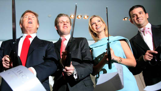In this April, 2010 file photo, Donald Trump, left, chairman and CEO of the Trump Organization, cuts the ribbon with his children Eric, Ivanka, and Donald Trump, Jr. right, at the opening of the Trump SoHo New York.