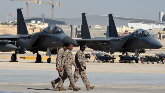 Saudi army officers walk past F-15 fighter jets, GBU bombs and missiles.
