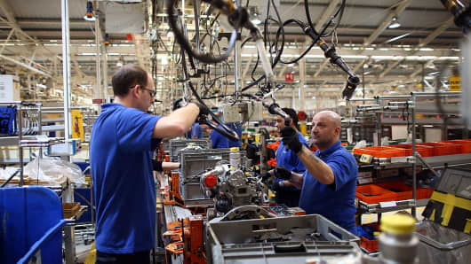 An employee works on an engine production line at a Ford factory on January 13, 2015 in Dagenham, England.