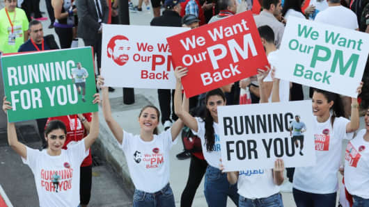 Supporters of Lebanon's resigned prime minister Saad Hariri hold up placards demanding his return from Saudi Arabia on the starting line of Beirut's annual marathon on November 12, 2017. Hariri announced on November 4 in a televised statement from Riyadh that he would be stepping down from the post, sending shock waves through Lebanese politics.