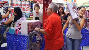 On the right, Diana Barrios navigates around the crowded entrance way as she and other early 'Black Friday' shoppers rush to shop at the 'Toys R Us' as the holiday season sales began on Thanksgiving Day, Nov. 23, 2017 in Doral, Fla.
