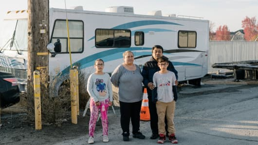 Adela Morales and Adrian Bonilla with their grandchildren Jaslene Orozco, 9, and Raul Orozco, 10, who live together in a recreational vehicle in East Palo Alto, Calif., Nov. 22, 2017. Wherever Facebook's co-founder Mark Zuckerberg goes in Silicon Valley, he seems to generate a housing problem, including at this RV community where residents were evicted this month.