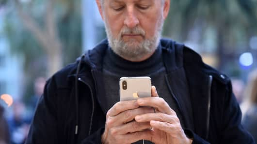 A customer views an Apple iPhone X smartphone at a store in San Francisco.