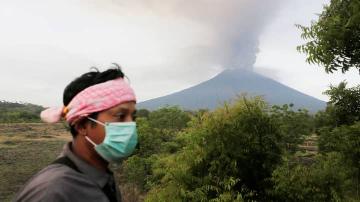 A villager walks as Mount Agung volcano erupts in the background in Kubu, Karangasem, Bali, Indonesia November 27, 2017.