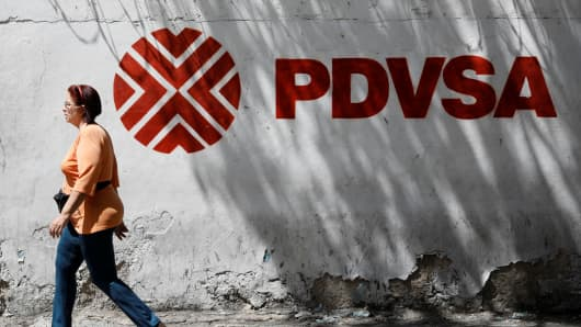 A woman walks past a mural with the corporate logo of the state oil company PDVSA in Caracas, Venezuela November 3, 2017.