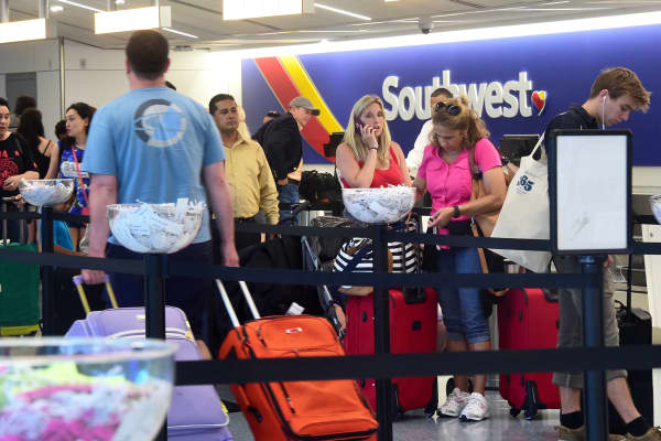 Travellers wait in line to check-in at a Southwest Airlines counter at Los Angeles International Airport.