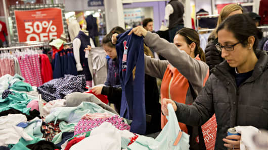 Shoppers look at clothes in a Vineyard Vines store at the Fashion Outlets of Chicago mall.