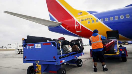 A ground operations employee loads baggage onto a Southwest Airlines plane at John Wayne Airport in Santa Ana, California.