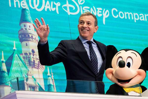 Chief executive officer and chairman of The Walt Disney Company Bob Iger and Mickey Mouse look on before ringing the opening bell at the New York Stock Exchange, November 27, 2017 in New York City.
