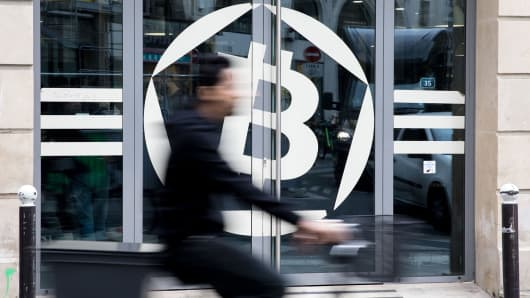 A cyclist passes the entrance to the La Maison du Bitcoin bank in Paris, France, on Thursday, Nov. 23, 2017.