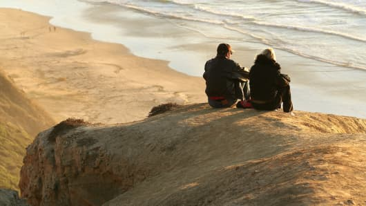 A couple watches the sunset in La Jolla, California.