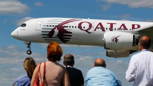 Visitors watch as Airbus A350 wide-body aircraft, produced by Airbus Group NV in Qatar Airways Ltd. livery, prepares to land.