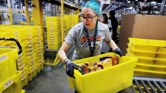A worker moves a bin filled with products inside of an Amazon fulfillment centre in Robbinsville, New Jersey.
