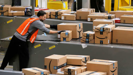 A worker prepares packages to be shipped inside of an Amazon fulfillment center in Robbinsville, New Jersey, November 27, 2017.