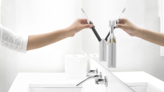 Quip electric toothbrushes hang on a bathroom mirror by a suction strip on the brush holder.