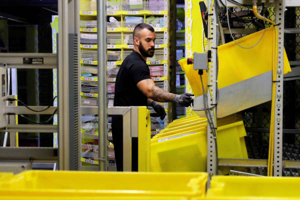 A worker sorts products into bins inside of a large Amazon fulfillment center in Robbinsville, New Jersey.