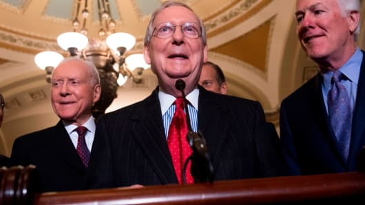 Senate Majority Leader Mitch McConnell (2nd R), alongside US Senator John Barrasso (L), Republican of Wyoming; and US Senator Orrin Hatch (2nd L), Republican of Utah, speaks after a meeting between US President Donald Trump and the Republican Senate Caucus at the US Capitol in Washington, DC, November 28, 2017.