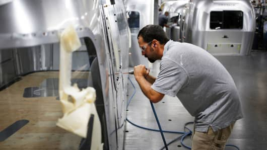 A factory worker installs rivets on an Airstream RV travel trailer at the company's assembly plant in Jackson Center, Ohio.