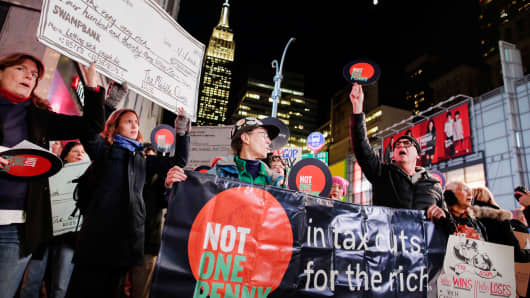 Demonstrators take part in a protest against tax cuts for rich people as the Empire State Building is seen at the background in New York City November 27, 2017.