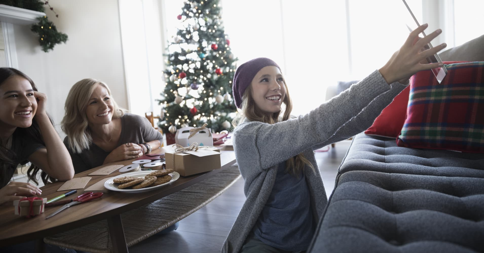 Smiling teenage girl with digital tablet taking selfie with mother and sister in Christmas living room