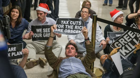 Protesters demonstrate near the full Senate budget committee markup of the tax reform legislation on Capital Hill November 28, 2017 in Washington, DC.