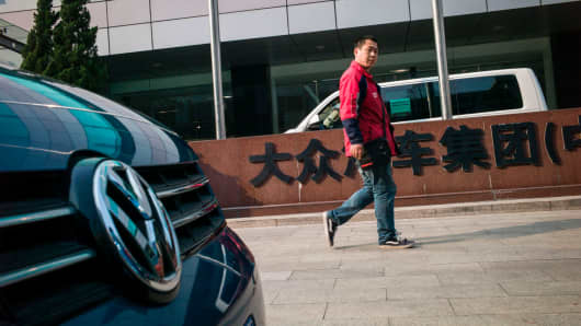 A man walks next to the Volkswagen Group China office in Beijing on March 29, 2017.