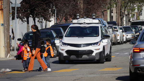 Children pass by a self-driving Chevy Bolt EV car during a media event by Cruise, GM's autonomous car unit, in San Francisco, November 28, 2017.