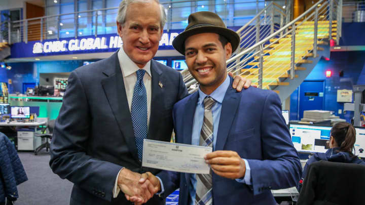 Robbie Cabral (r) founder and CEO of BenjiLock holds up a check for $100,000 from Kim Kelley, CEO of Hamptons Products.