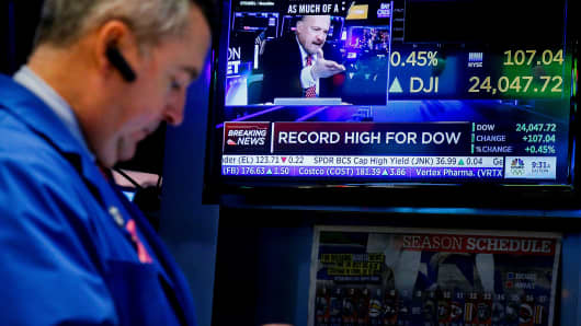 Traders work on the floor of the New York Stock Exchange, (NYSE) as a screen displays the Dow Jones Industrial Average as it crosses 24,000, in New York, U.S., November 30, 2017.