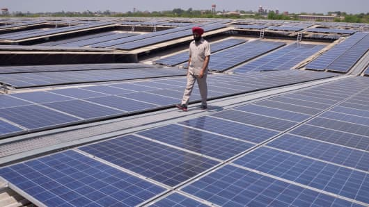 An Indian security personnel walks over rooftops covered in solar panels at the Solar Photovoltaic Power Plant near Amritsar, India.