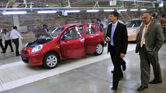 Visitors inspect Nissan Micra cars at the newly-inaugurated Renault and Nissan auto plant in Chennai, India on March 17, 2010.