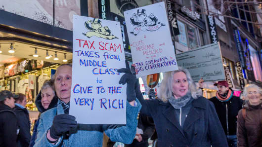 Over a hundred protesters met at Greeley Square in Midtown Manhattan on November 27, 2017 and marched along 34th Street behind a Not One Penny of Tax Cuts for the Rich banner, with Tax Scam signs, Not One Penny signs and giant checks made out from Medicaid or Medicare to billionaires or corporations, to raise awareness against the irresponsible tax plan that cuts Medicare and increases healthcare costs for older New Yorkers.