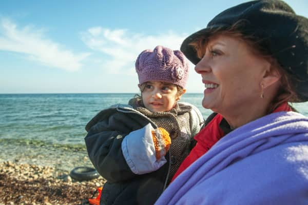 Susan Sarandon holding a baby at a refuge camp in Greece.