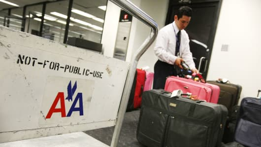 An American Airlines employee scans baggage at the San Francisco International Airport.