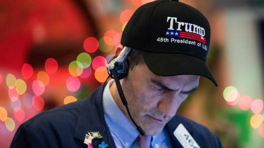 A trader wears a 'Trump' hat as he works on the floor of the New York Stock Exchange (NYSE) ahead of the closing bell, November 30, 2017 in New York City.