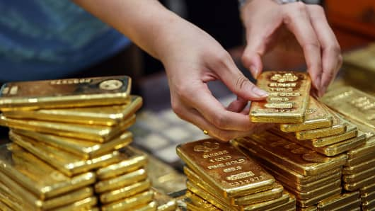 An employee arranges gold bars for a photograph at the YLG Bullion International headquarters in Bangkok, Thailand, on January 13, 2016.