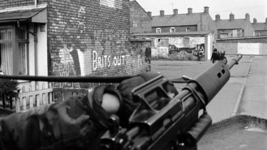 A British Army mobile patrol moves past IRA graffiti in the Republican Ardoyne district of north Belfast, 19th April 1976.