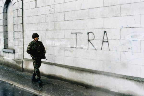 The British Army In Northern Ireland, 1969 - 2007, A soldier on patrol walks past IRA graffiti sprayed onto a wall in Newry, County Down, circa 1986.