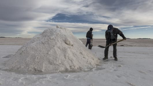 Employees shovel salt into mountains at the Salar de Uyuni (Uyuni Salt Flats) in Potosi, Bolivia, on Sunday, Dec. 11, 2016.