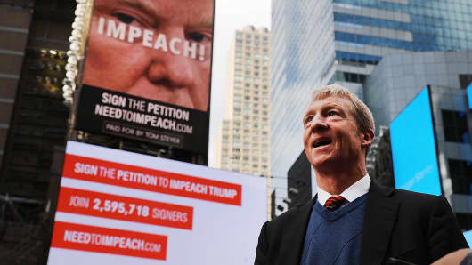 Philanthropist Tom Steyer stands in front of one of the billboards he has funded in Times Square calling for the impeachment of President Donald Trump on November 20, 2017 in New York City.