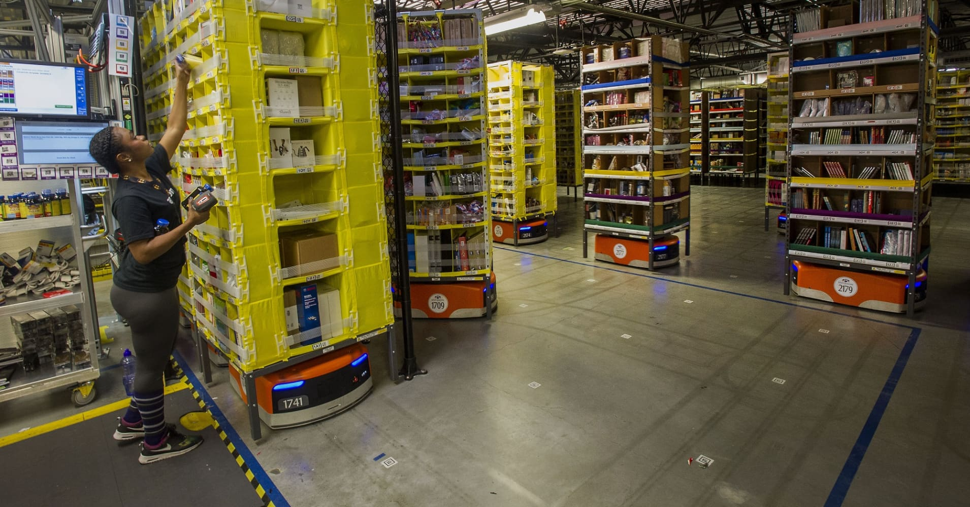 An employee packs shelves as Kiva Systems LLC robots move them to fill orders at the Amazon fulfillment center in Tracy, California.