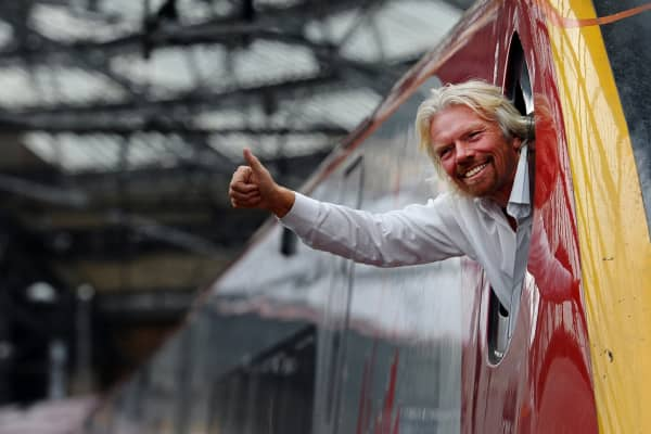 British entrepreneur Sir Richard Branson leans out of the window of the driver's cab on board a Virgin Pendolino train at Lime Street Station in Liverpool, north-west England, on March 13, 2012, as he prepares to launch a Global Entrepreneurship Congress.