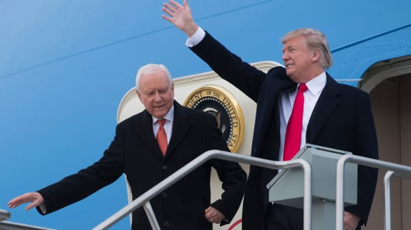 President Donald Trump waves alongside US Senator Orrin Hatch (L), Republican of Utah, as they disembark from Air Force One upon arrival at Salt Lake City International Airport in Utah, December 4, 2017.