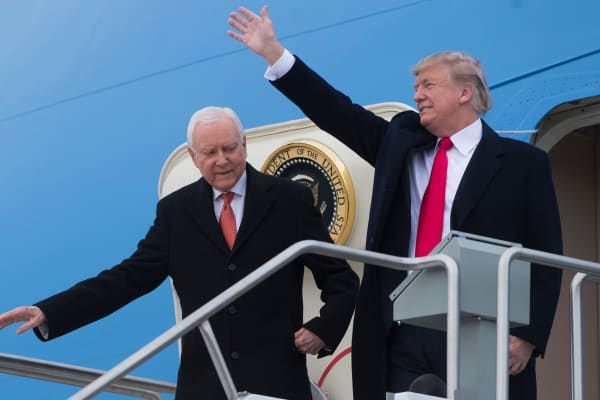 President Donald Trump waves alongside US Senator Orrin Hatch (L), Republican of Utah, as they disembark from Air Force One upon arrival at Salt Lake City International Airport in Utah, December 4, 2017.