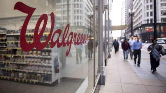 Pedestrians pass in front of a Walgreens store in Chicago.