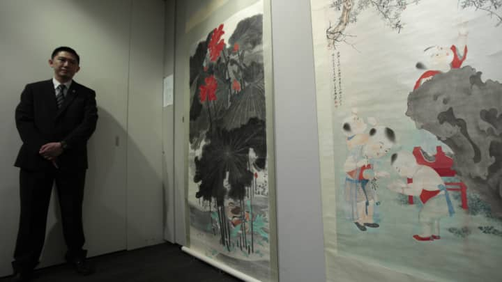 "A security guard stands next to paintings titled ""Lotus and Mandarin Duck"" (L) and ""Children Playing under a Pomegranate Tree,"" by Chinese artist Zhang Daqian."