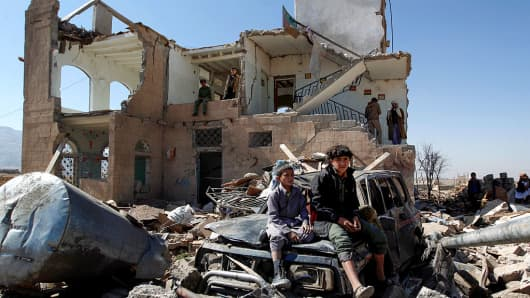 Children sit amidst the rubble of a house hit by Saudi-led coalition air strikes two days earlier on the outskirts of the Yemeni capital Sanaa on November 14, 2016.