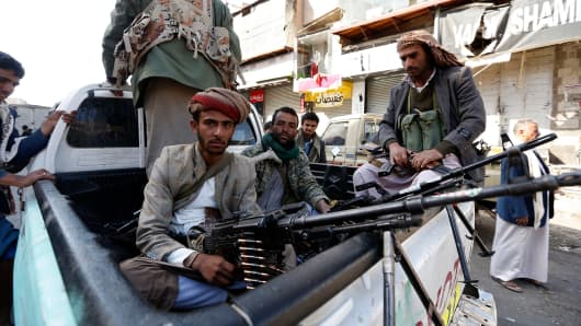 Huthi rebel fighters are seen riding an armoured vehicle in front of the residence of Yemen's former President Ali Abdullah Saleh in Sanaa on December 4, 2017.