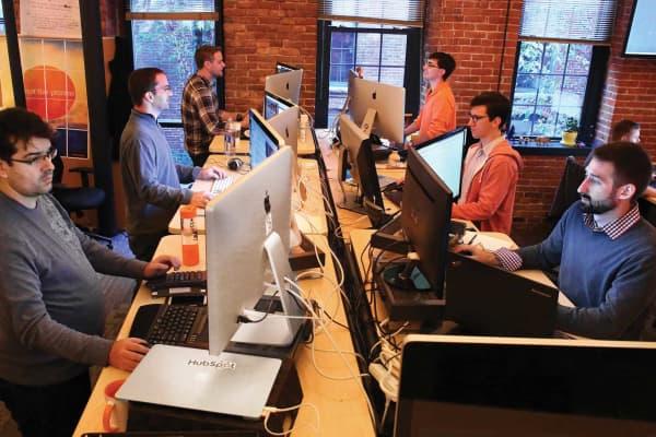 HubSpot employees work at their standing desks in Cambridge, Mass.