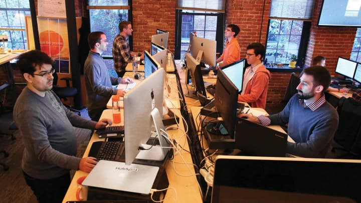 HubSpot emploуees work at their standing desks in Cambridge, Mass.